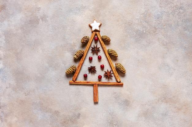 Originaler weihnachtsbaum aus zimtstangen, roten beeren, zapfen und sternförmigen keksen