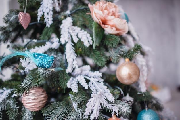 Originelles dekor und spielzeug hängen am reichen weihnachtsbaum, der in einem gemütlichen raum steht