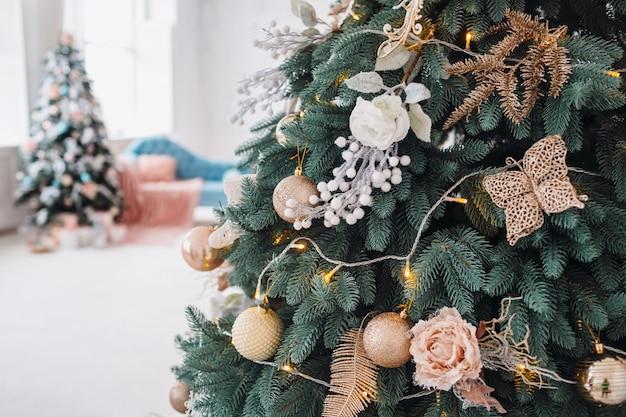 Originelles dekor und spielzeug hängen am reichen weihnachtsbaum
