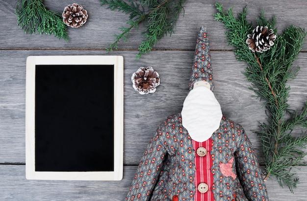 Ornament santa claus im mantel in der nähe von fotorahmen, zweigen und baumstümpfen