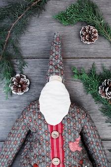 Ornament santa claus im mantel zwischen zweigen und baumstümpfen