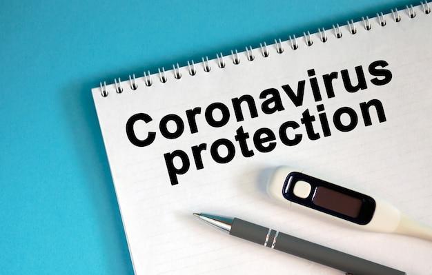 Ð¡oronavirus-schutz - text auf einem notizblock. liegen ein stift und ein medizinisches thermometer