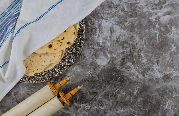 Orthodoxer jude vorbereitet mit tora scrolls koschere matze am traditionellen jüdischen passahfest