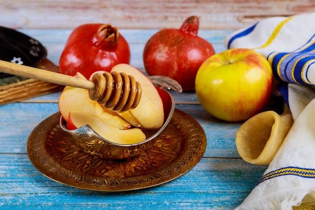 Orthodoxer jüdischer feiertagshonig auf dem granatapfel und den äpfeln. jüdisches neues jahr rosh ha shana shofar