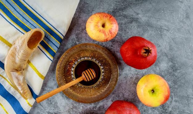 Orthodoxer jüdischer feiertagshonig auf dem granatapfel und den äpfeln