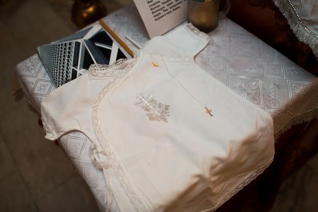 Orthodoxes christliches kreuz und kleid für kleines kind in der kirche. ritus der epiphanie-zeremonie.