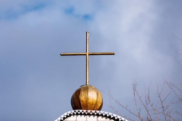 Orthodoxes kirchenkreuz auf einem hintergrund des blauen himmels mit wolken. ostern. weihnachten. platz für text. hintergrundbild. religion. selektiver fokus