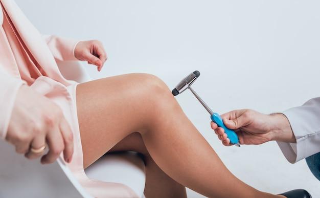 Orthopäde, die den kniereflex untersucht. der arzt überprüft den physiologischen reflex. hammer testen