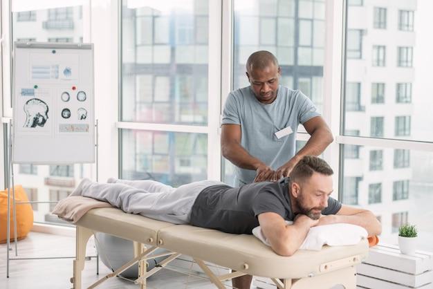 Orthopäde. geschickter netter starker mann, der nahe seinem patienten steht, während er eine wirbelsäulenmassage für ihn tut