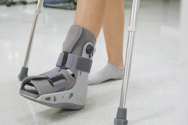 Orthopädischer stiefel und krücke zu einem patienten. medizinisches orthopädisches konzept.