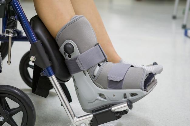 Orthopädischer stiefel zu einem patienten. medizinisches orthopädisches konzept.