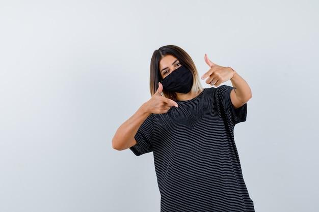 Ortrait der dame, die auf kamera im schwarzen kleid, in der medizinischen maske und in der selbstbewussten vorderansicht zeigt