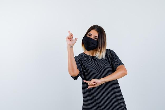 Ortrait der dame, die im schwarzen kleid, in der medizinischen maske und in der hoffnungsvollen vorderansicht nach oben zeigt