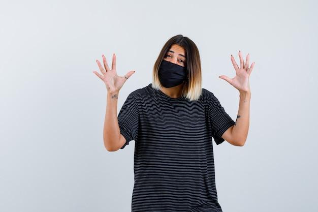 Ortrait der dame, die vorgibt, etwas im schwarzen kleid, in der medizinischen maske und in der selbstbewussten vorderansicht zu zeigen