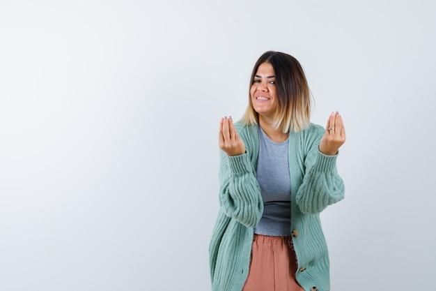 Ortrait der frau, die italienische geste in der freizeitkleidung tut und glückliche vorderansicht schaut