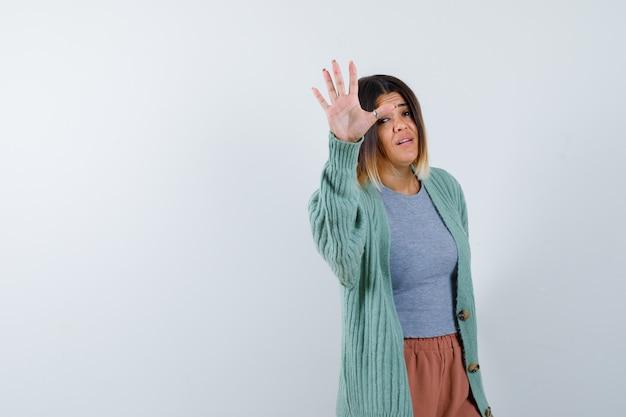 Ortrait der frau, die stoppgeste in der freizeitkleidung zeigt und selbstbewusste vorderansicht schaut