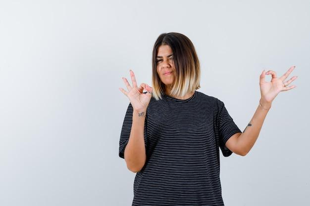 Ortrait der jungen dame, die ok geste im polokleid zeigt und selbstbewusste vorderansicht schaut