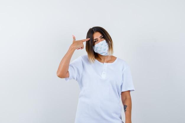 Ortrait der jungen frau, die auf kopf im t-shirt, in der maske und in der nachdenklichen vorderansicht zeigt