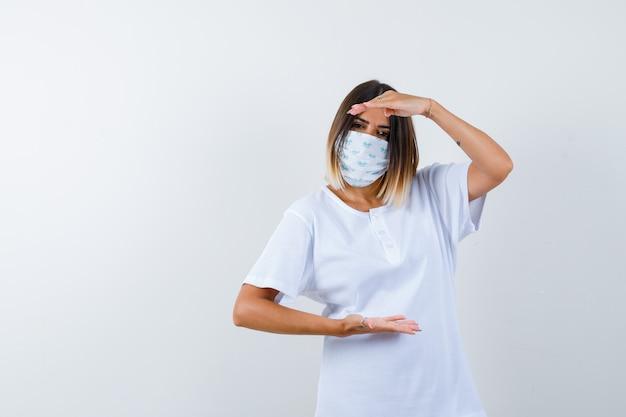 Ortrait der jungen frau, die größenzeichen im t-shirt, in der maske und in der selbstbewussten vorderansicht zeigt