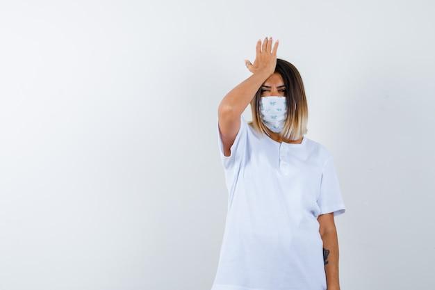 Ortrait der jungen frau, die hand auf kopf im t-shirt, in der maske und in der vergesslichen vorderansicht hält