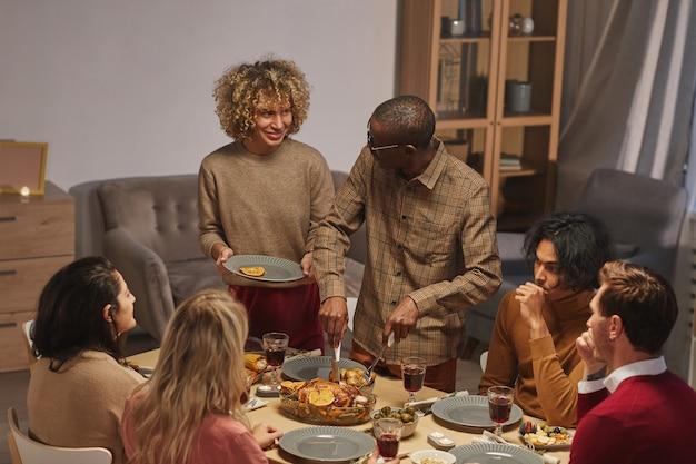 Ortrait des lächelnden afroamerikanischen mannes, der gebratenen truthahn schneidet, während thanksgiving-abendessen mit freunden und familie genießt,