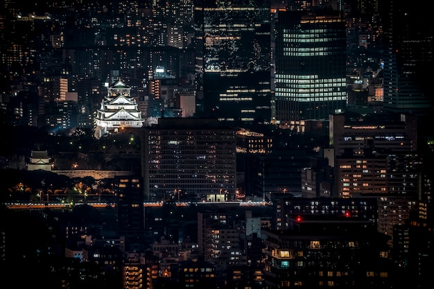 Osaka castle beleuchtet in der nacht in birdeye oder draufsicht mit stadtbild und hohem gebäude herum, präfektur osaka, japan.