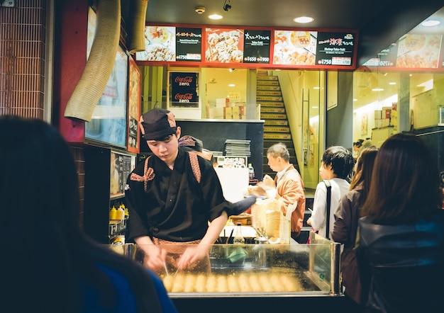 Osaka, japan - 1. september: nicht identifizierte köche bereiten takoyaki