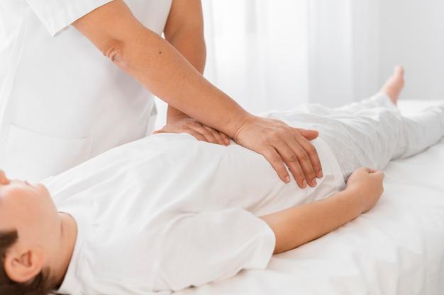 Osteopath behandelt ein kind, indem er seinen körper massiert