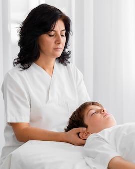 Osteopath behandelt ein kind, indem er seinen kopf massiert