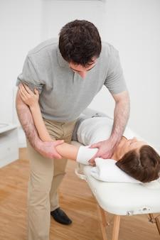 Osteopath, der an einer schulter eines patienten arbeitet