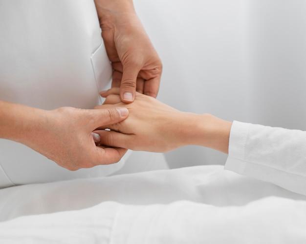 Osteopath, der den arm eines patienten behandelt
