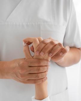 Osteopath, der die arme eines patienten behandelt