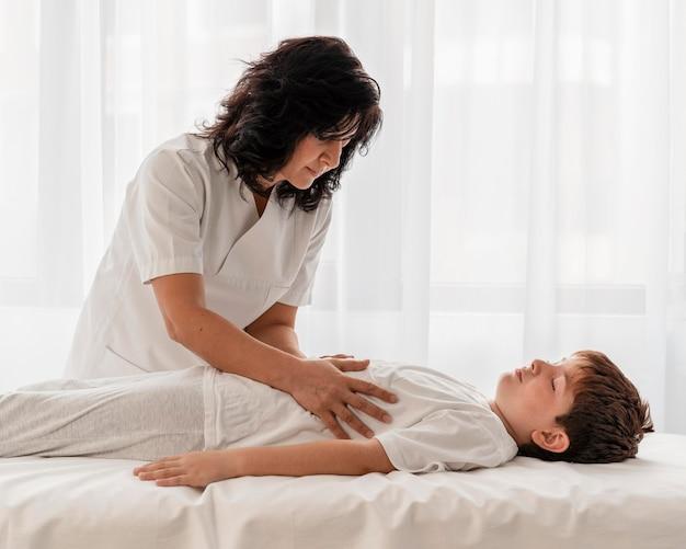 Osteopath, der die beine eines kindes im krankenhaus behandelt