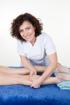 Osteopath, der druck mit daumen auf den weiblichen muskel ausübt