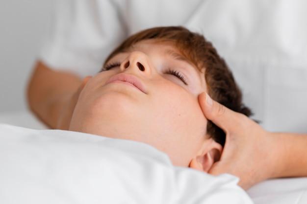 Osteopath, der ein kind behandelt, indem er seinen kopf massiert