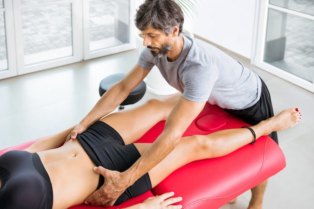Osteopath, der eine beurteilung der beckenausrichtung an einer jungen patientin auf einer couch in seiner praxis oder klinik in einem medizinischen und medizinischen konzept durchführt