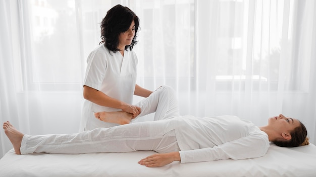 Osteopath, der eine junge frau im krankenhaus behandelt