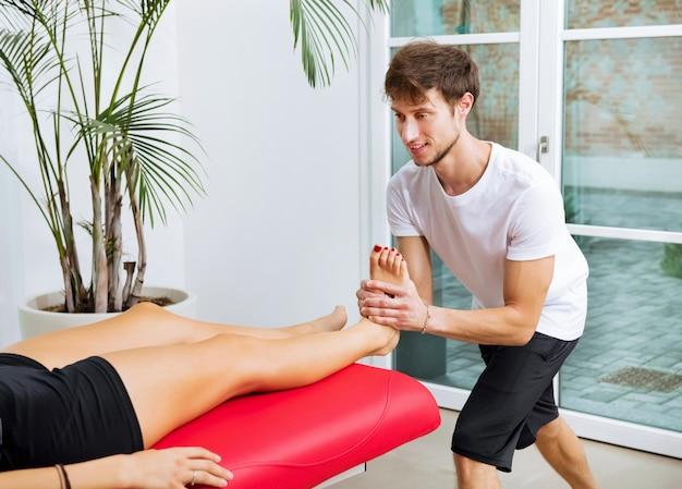 Osteopath, der eine knöcheldekontraktion an einer jungen patientin durchführt