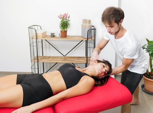 Osteopath, der einer patientin, die während einer konsultation in seiner klinik ihre wirbelsäule manipuliert, zervikales vertrauen entgegenbringt