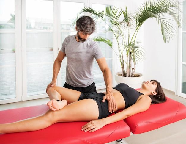 Osteopath, der in seiner klinik eine hüftuntersuchung durchführt, um die beweglichkeit und funktion des gelenks bei einer jungen patientin auf einer couch zu überprüfen Premium Fotos