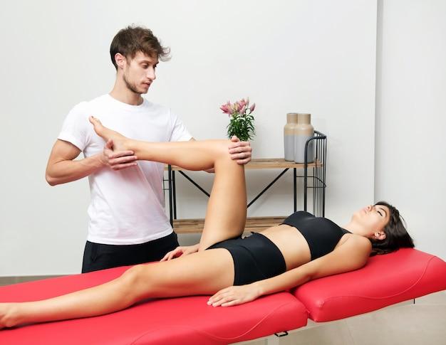 Osteopathin führt eine hüftuntersuchung an einer patientin durch, die ihr bein beugt, um die beweglichkeit des gelenks und die ausrichtung des beckens zu überprüfen, während sie auf einer couch in seiner klinik liegt