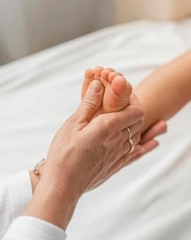 Osteopathist, der die füße eines kleinen mädchens behandelt