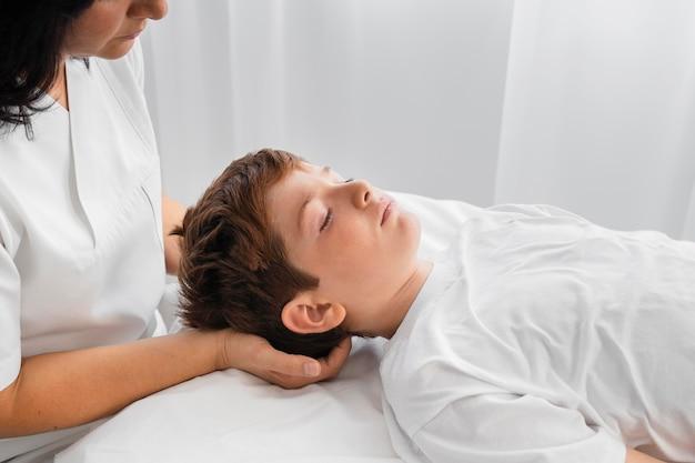 Osteopathist, der ein kind im krankenhaus behandelt