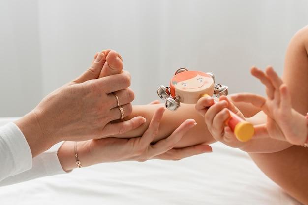 Osteopathist, der ein kleines mädchen behandelt, das mit einer holzpuppe spielt