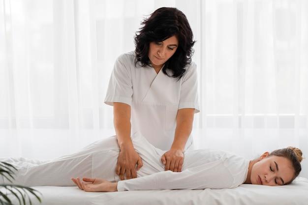 Osteopathist, der eine frau drinnen behandelt