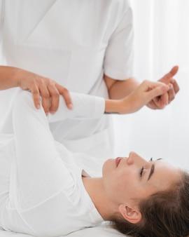 Osteopathist, der eine junge frau drinnen behandelt