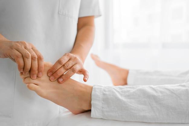 Osteopathist, der einen patienten auf seinen füßen behandelt