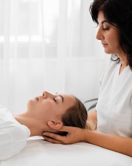 Osteopathist, der einen patienten drinnen behandelt