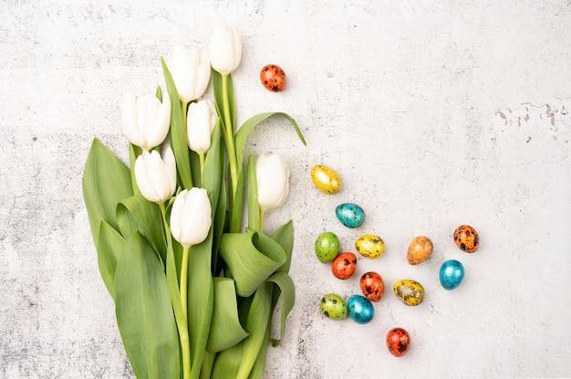 Oster- und frühlingskonzept. draufsicht auf weiße tulpen und farbige ostereier auf betonhintergrund mit kopierraum