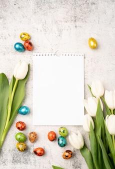 Oster- und frühlingskonzept. draufsicht der weißen tulpen, des leeren kalenders und der farbigen ostereier auf betonhintergrund mit kopienraum